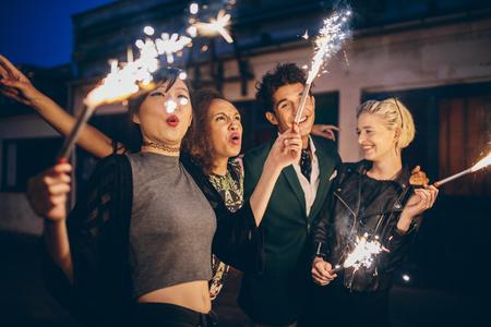 Groep vrienden genieten met sterretjes op stadsstraat. Jonge mensen genieten van oudejaarsavond met vuurwerk. Stockfoto