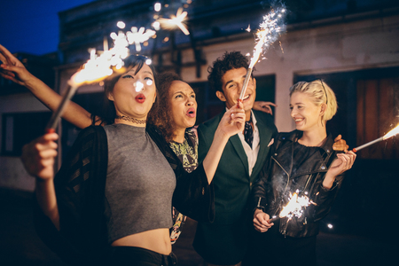 Group of friends enjoying out with sparklers on city street. Young people enjoying new years eve with fireworks.