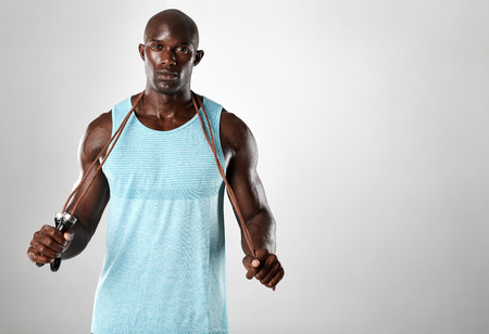 African fitness model with skipping rope against grey background. Handsome muscular man posing with jumping rope. Imagens