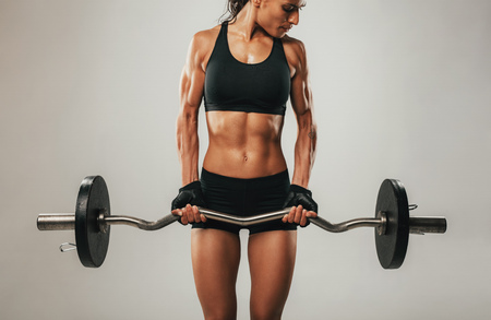 straining: Muscles bulging on arms of muscular young woman using barbell weight