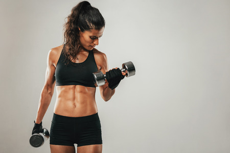Sweaty muscular woman with pony tail hair style and shorts curling dumbbell over gray background with copy space