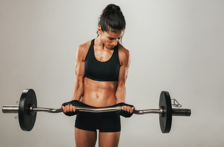 Strong young woman lifting barbell for bicep strengthening over gray background with copy space