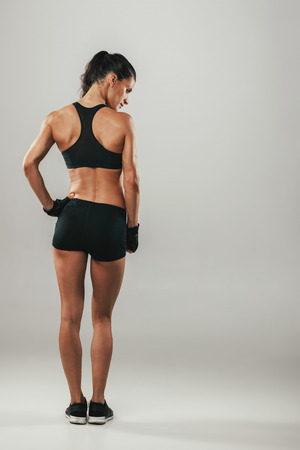 Back side view of woman in sports shorts and top looks over her shoulder while standing against a grey background Stock Photo