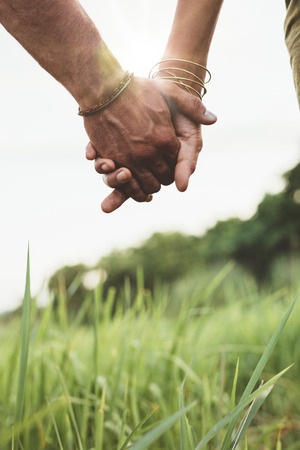 Vertical shot of young couple walking through meadow hand in hand with sun flare. Close up shot with focus on hands of man and woman.