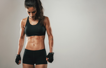 healthy looking: Fit healthy young female athlete with a toned strong body standing looking down, cropped three quarter view on grey with copy space