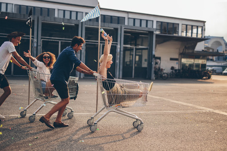 Young friends having fun on a shopping trolley. Multiethnic young people racing on shopping cart.
