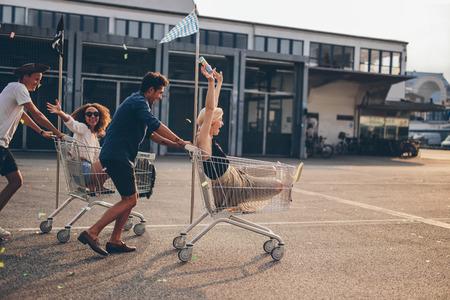 Jonge vrienden plezier op een winkelwagentje. Multi-etnische jongeren racen op winkelwagen.