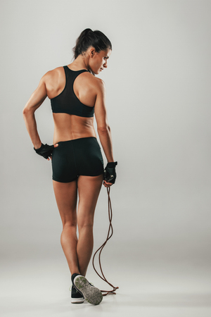 feet crossed: Fit healthy athletic woman with a skipping rope viewed from behind in her sportswear standing with crossed feet, over grey with copy space