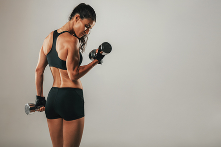 Fit strong young woman lifting weights working out with dumbbells standing with her back to the camera flexing her arm on grey with copy space Stock Photo