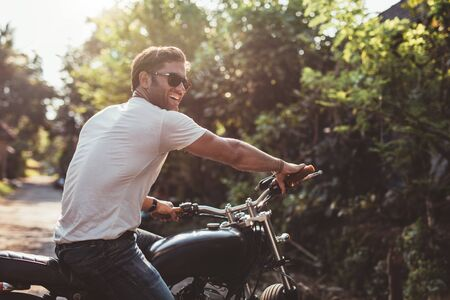 Portrait of handsome young man on motorcycle. Happy caucasian male on motorbike looking away and smiling.
