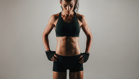 weightlifting gloves: Trim abdominal muscles of woman with gloved hands on hips over gray background with copy space