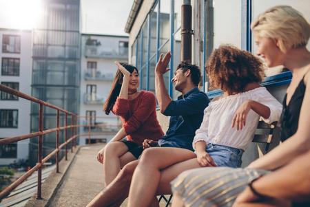 발코니에서 재미와 높은 5주고 친구의 Multiracial 그룹. 테라스에서 즐기는 젊은 사람들.