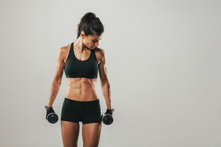 weightlifting gloves: Attractive woman holding dumbbells facing sideways while preparing mentally for intense training over gray background with copy space