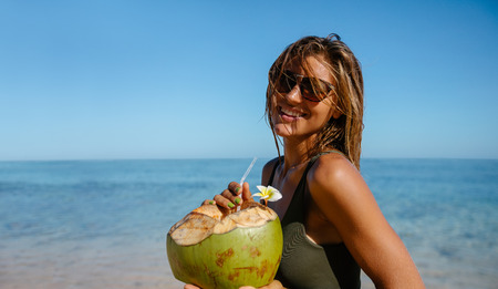 Portrait of beautiful young woman with fresh coconut on the beach. Caucasian woman wearing sunglasses having fresh coconut water on the sea shore. Stock Photo
