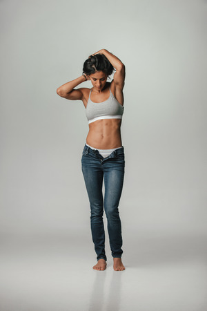 undone: Trendy young woman posing in underwear and jeans with her zip undone to disclose her panties standing barefoot with her arms raised to her head showing her toned fit body, over grey
