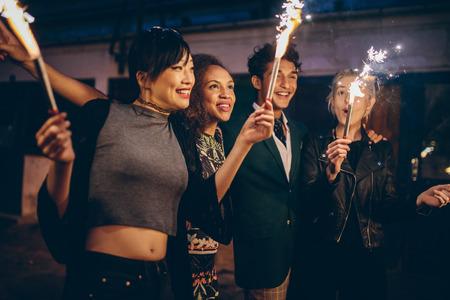 Cuatro jóvenes amigos celebrando la víspera de año nuevo con fuegos artificiales. Grupo de personas que disfrutan con bengalas en las carreteras de la tarde.