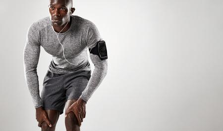fitness hombres: Hombre africano joven con brazalete y auriculares de pie sobre fondo gris y mirando a otro lado.