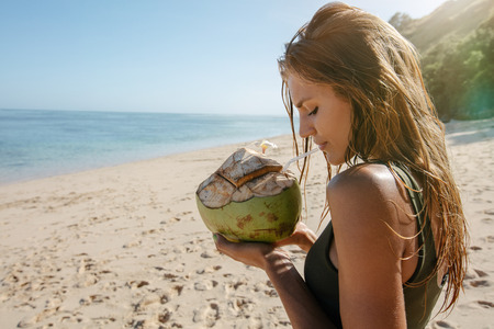 sea side: Side view shot of young woman holding coconut on sea shore. Female tourist on beach vacation.