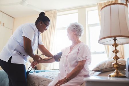 Female nurse doing blood pressure measurement of a senior woman patient. Doctor checking blood pressure of an elderly woman at old age home. photo