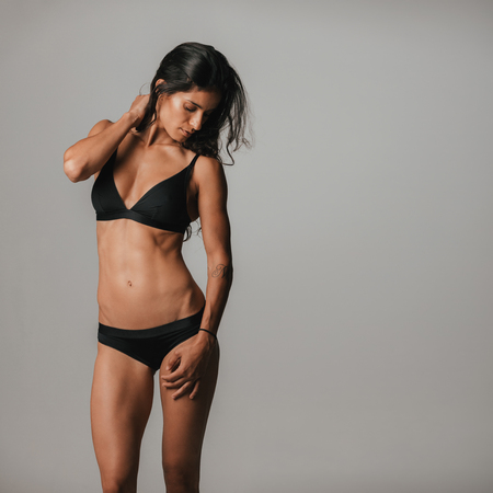 Beautiful tanned woman wearing black under garment stands in grey room