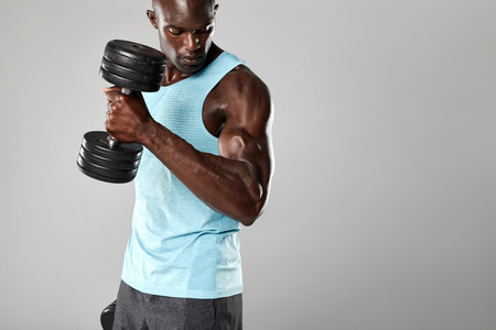 フィット感と灰色の背景にダンベル扱う若い男のショット。重量運動を行う筋肉男。