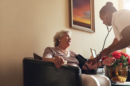 Home healthcare nurse checking blood pressure of senior woman. Elderly woman sitting on chair at home with female caregiver taking her blood pressure. photo
