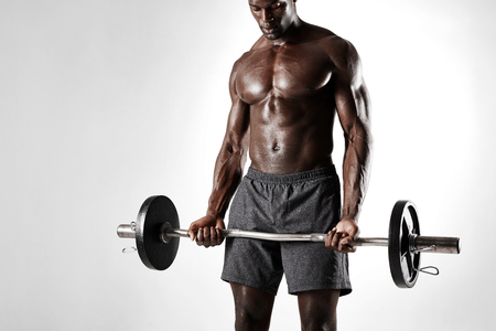 sportsmen: Studio shot of black man lifting weights against grey background. African sportsman exercising with barbell.
