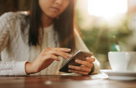 cafe internet: Mujer asiática joven que se sienta en una tabla usando el teléfono móvil. Teléfono inteligente en manos de una mujer en el café al aire libre.