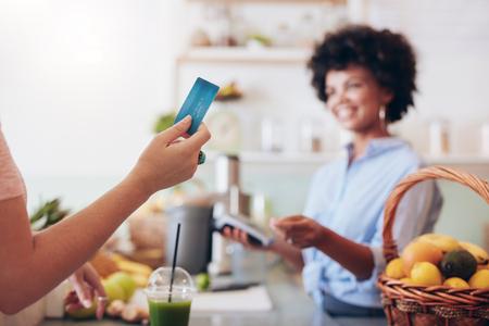 payer à la clientèle pour leur commande avec une carte de crédit dans un bar à jus. Bartender tenant une machine de lecteur de carte de crédit en arrière-plan. Focus sur la carte de crédit dans la main de la femme.