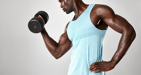 hand weights: Mixed race man exercising with hand weights against grey background. Young fit man lifting a dumbbell. Stock Photo