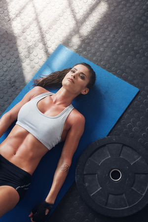 heavy weight: Top view of muscular female lying on exercise mat with a heavy weight plate on floor. Fitness woman relaxing after heavy weight workout. Stock Photo