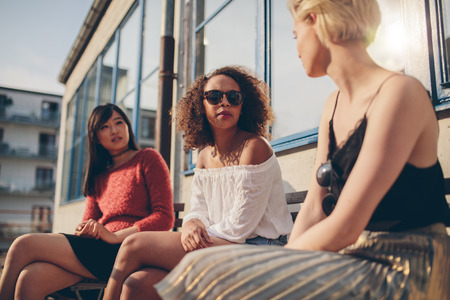 chatting: Three young female friends meeting outdoors. Multiracial group of young women sitting outdoors and chatting.