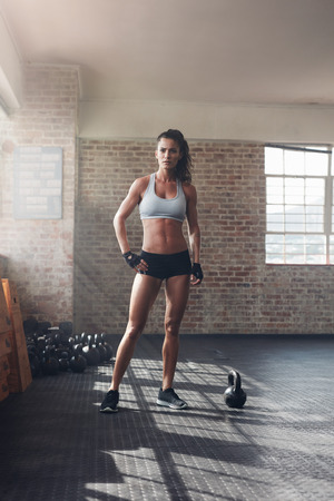Full length shot of muscular woman standing in crossfit gym and looking confident. Tough fitness female model with kettle bell on floor. Stock Photo