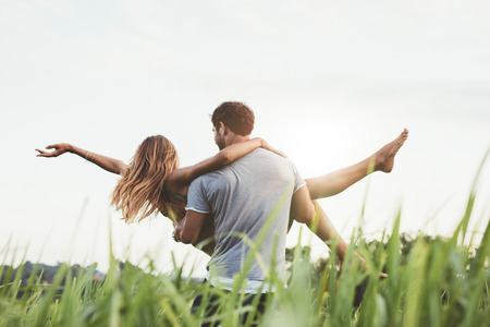 Rear view shot of man carrying woman in rural field. Couple enjoying outdoors on grass field. Stock Photo
