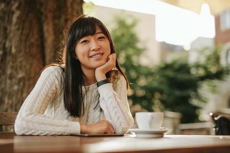 exteriores: Tiro de la muchacha atractiva que se sienta en la mesa de café y sonriente. Mujer joven que mira a la cámara mientras se relaja en cafetería al aire libre. Foto de archivo