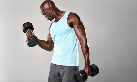 pesas: Foto de hombre musculoso joven haciendo ejercicios de pesas pesadas para los bíceps. modelo de la aptitud africano que trabaja con pesas en el fondo gris.
