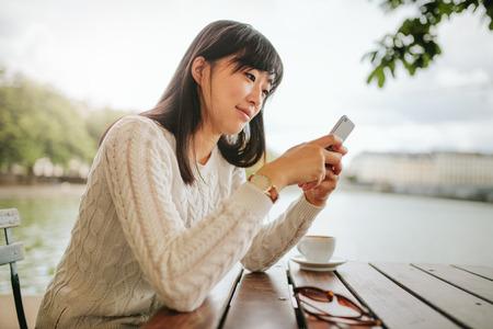 美しいアジアの女性のカフェで携帯電話を使用しての撮影。スマート フォンを使用した屋外のコーヒー テーブルに座っている若い女性。