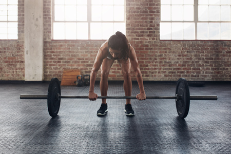 snatch: Full length of an fit young woman working out with a barbell at the gym. Bodybuilder female exercising at the gym.