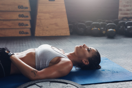 break: Shot of fit young woman relaxing on exercise mat. Healthy female athlete taking a break during her fitness training.