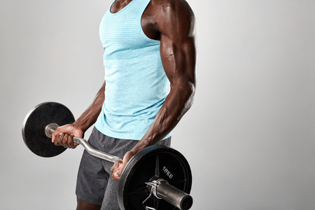 cropped shot: Cropped shot of african man exercising barbell against grey background. Muscular man lifting weights.