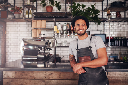 coffeeshop: Proud coffee shop owner at the counter. Coffee shop worker in apron and hat leaning to counter. Stock Photo