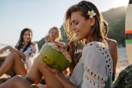 Side portrait of attractive young woman drinking coconut juice with her friends sitting in background. Young people relaxing on the beach on summer vacation. Imagens