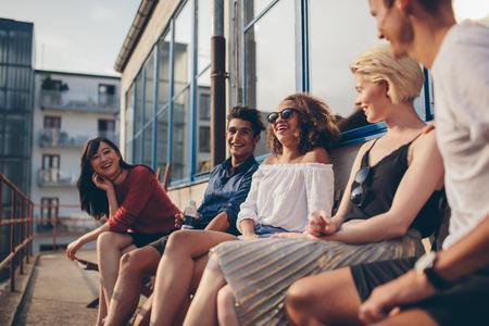 personas sentadas: Grupo multirracial de amigos sentados en el balcón y la sonrisa. Los jóvenes relajan al aire libre en la terraza. Foto de archivo