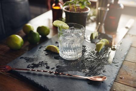 Close-up van glas van een vers bereide gin-tonic met schijfjes citroen en lepel op de teller.