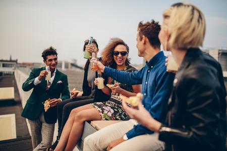 Multiethnische Gruppe von jungen Freunden auf der Terrasse feiern, trinken und feiern. Junge Männer und Frauen mit Getränken auf dem Dach
