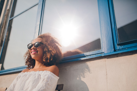 outdoor outside: Outdoor shot of happy young african female sitting outdoors and smiling. Woman wearing sunglasses sitting outside her house.