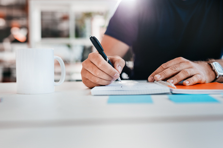 Cropped shot of man writing on notepad. Hand of businessman taking notes while sitting at his desk in office.