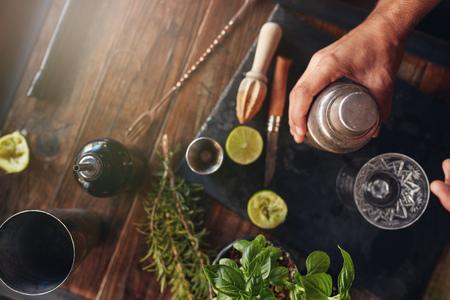 Vista superior del tiro de la mano camarero de celebración coctelera en la mesa con los ingredientes.