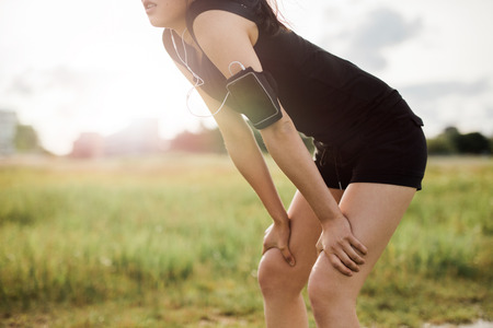 sports gear: Young woman leaning over in sports gear. Determined sports woman looking forward for run.