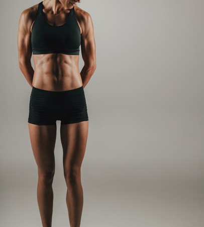 shadowed: Fit toned strong young woman flexing her abdominal muscles in shadowed light over grey in a closeup cropped view Stock Photo